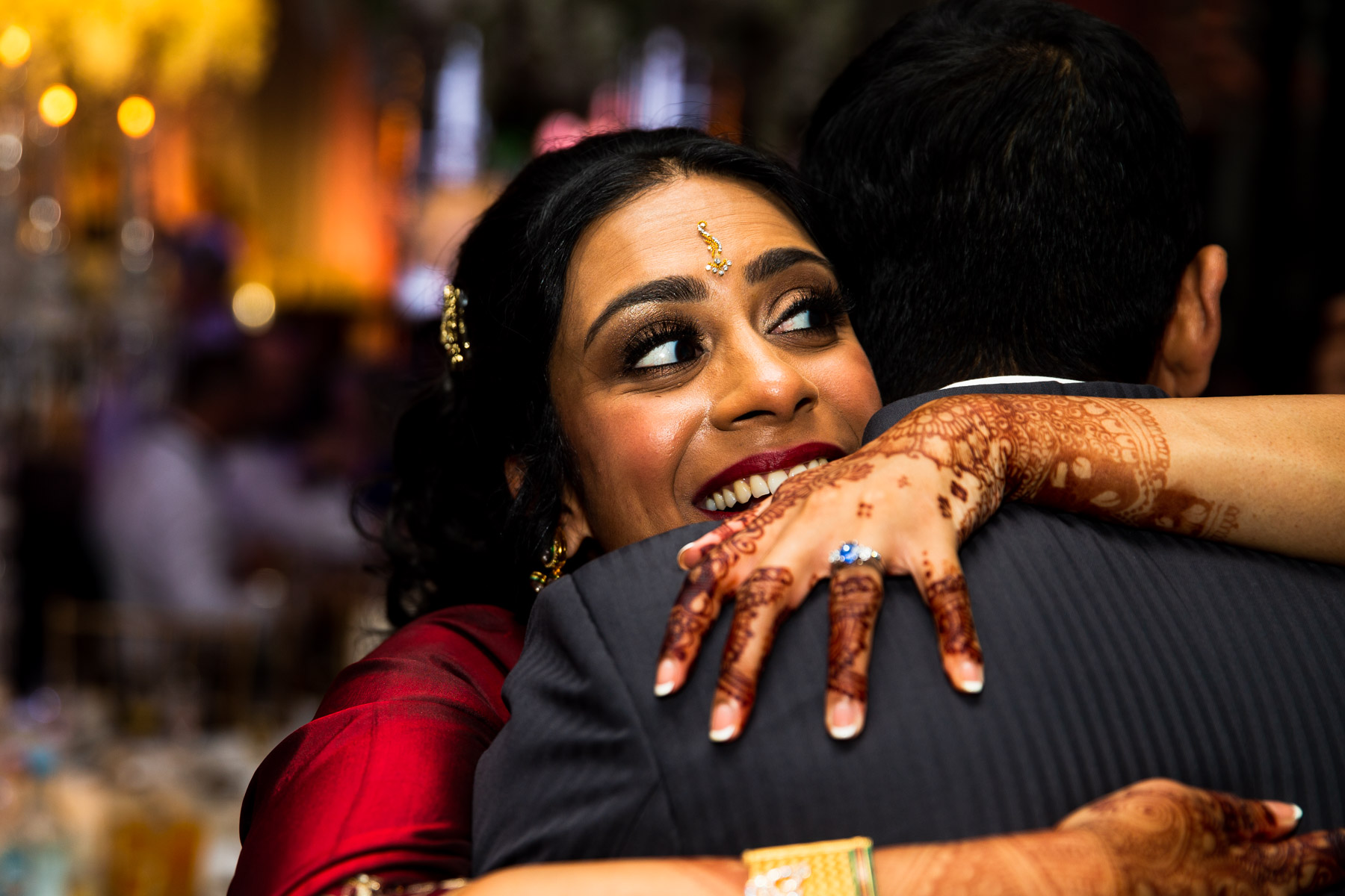 Intimate moment of wedding bride hugging guest