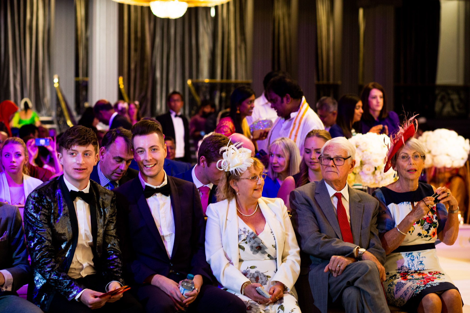 Colourful and relaxed wedding guests waiting for bride and groom