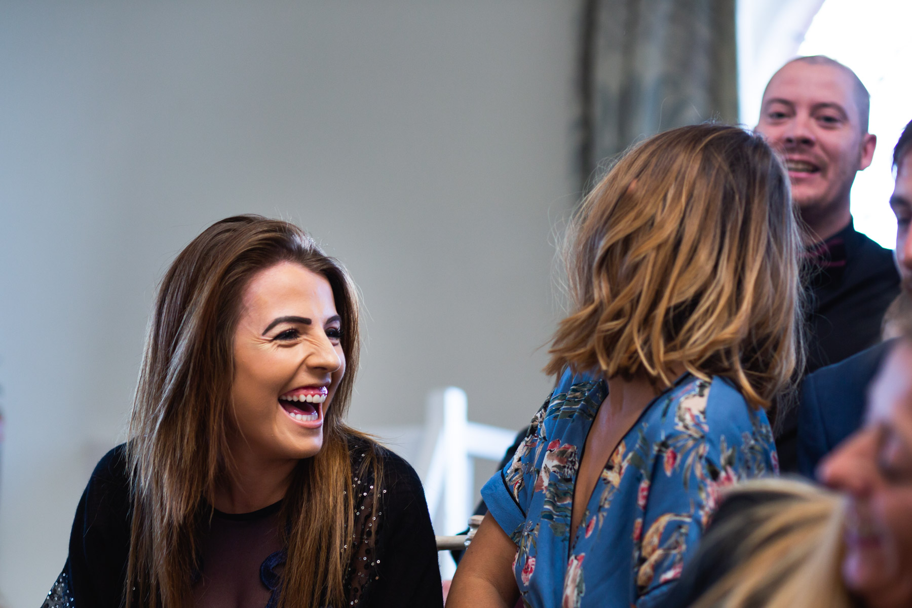 Guests laughing at joke at wedding ceremony