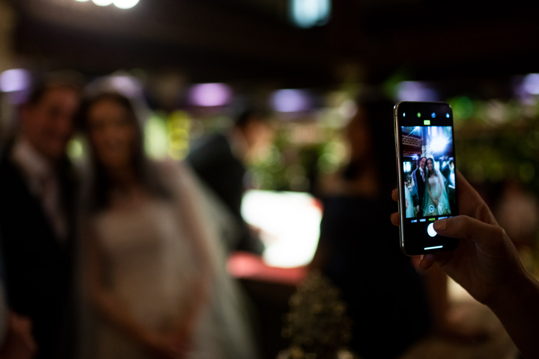 Intimate moment of guest taking photo of wedding couple