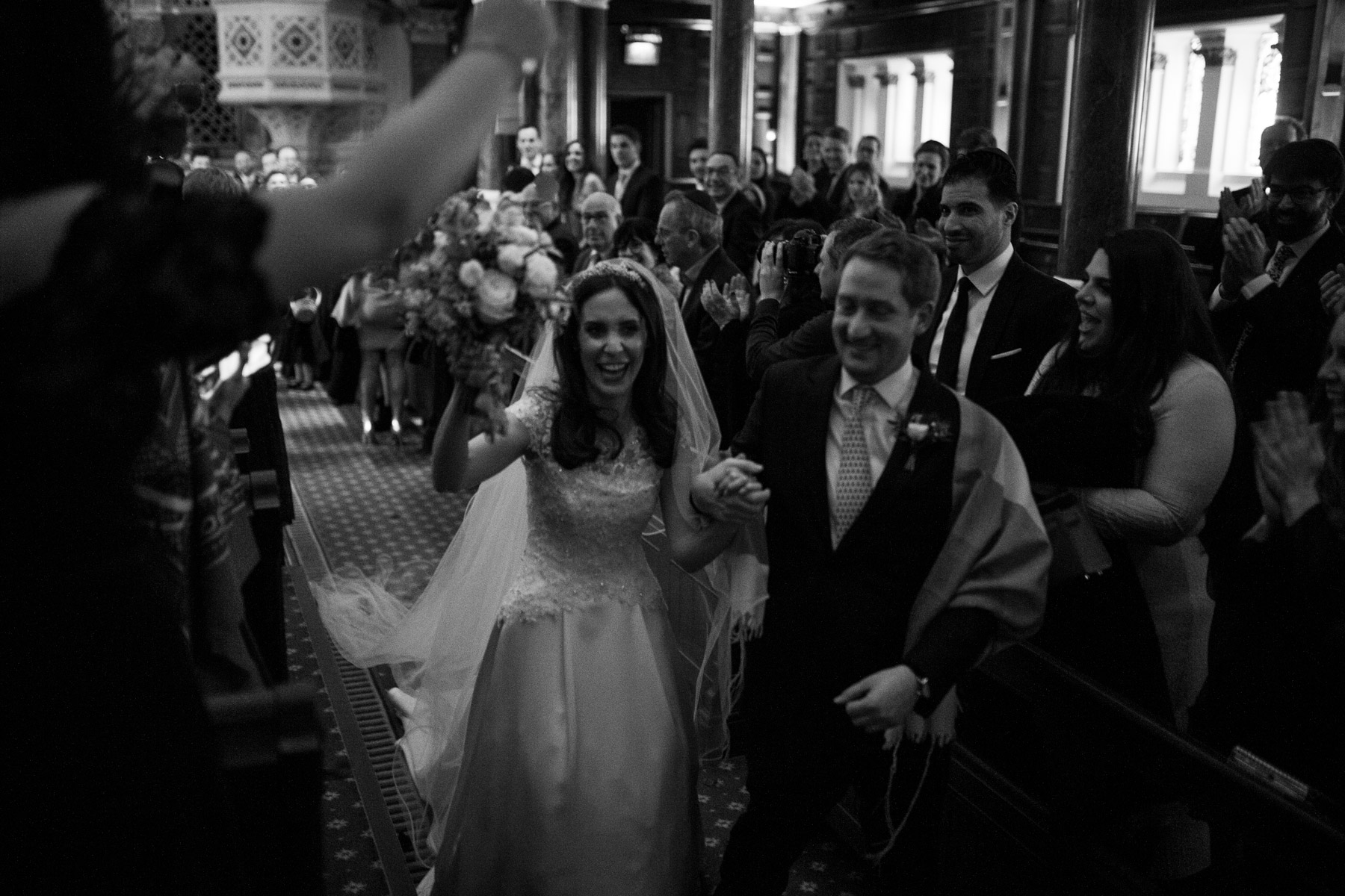 Relaxed and intimate moment of bride and groom leaving wedding ceremony