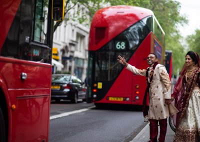 Fun photo of bride and groom with red London bus