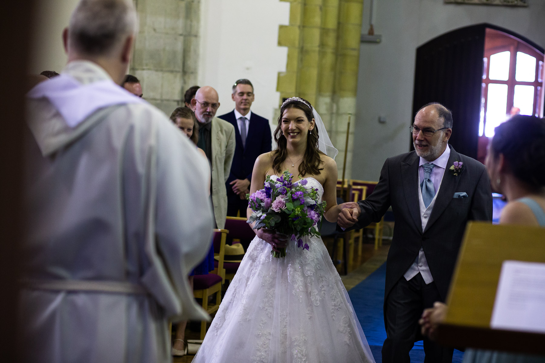 Relaxed bride and father walking down the aisle