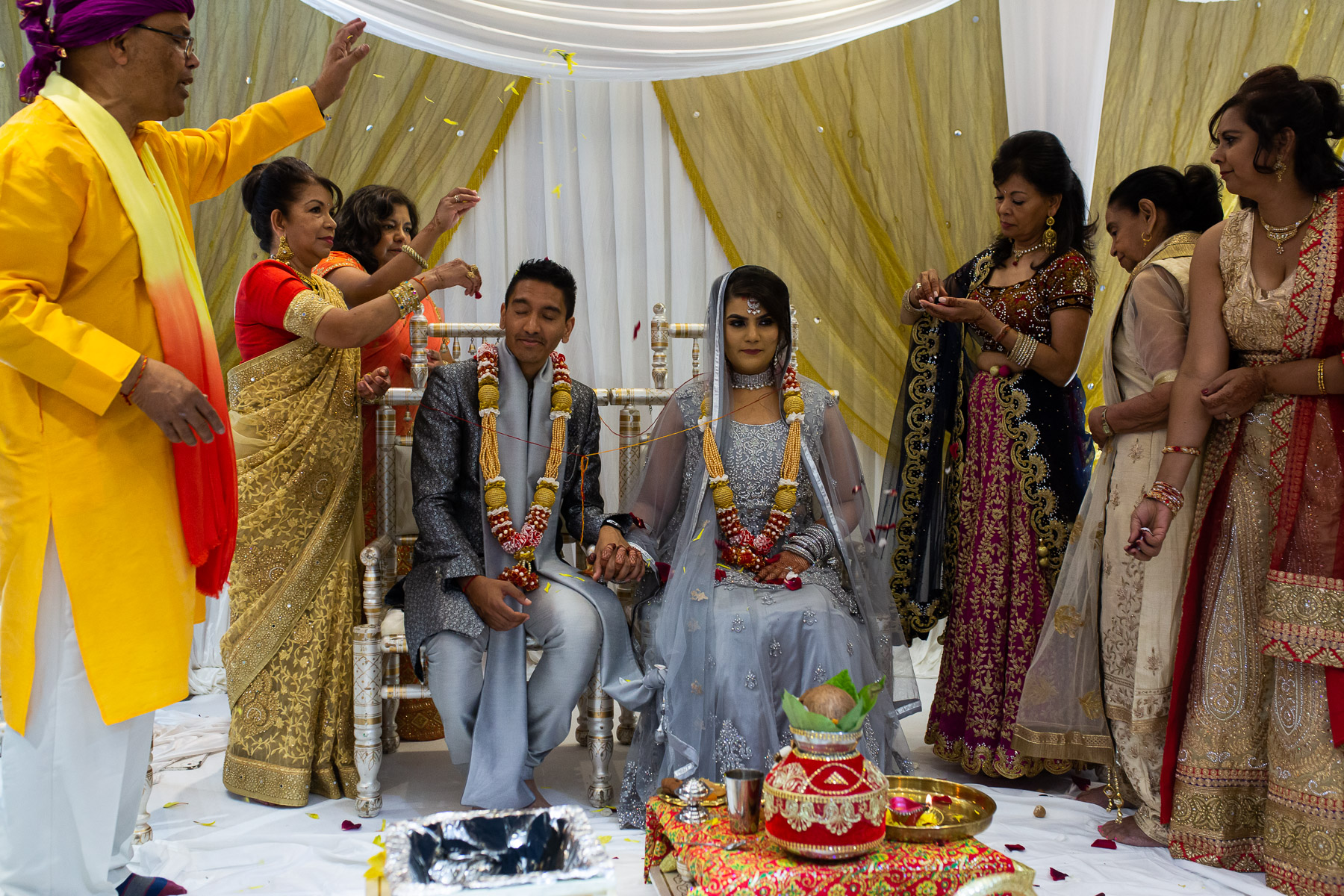 Bride and groom at Asian wedding with family around them