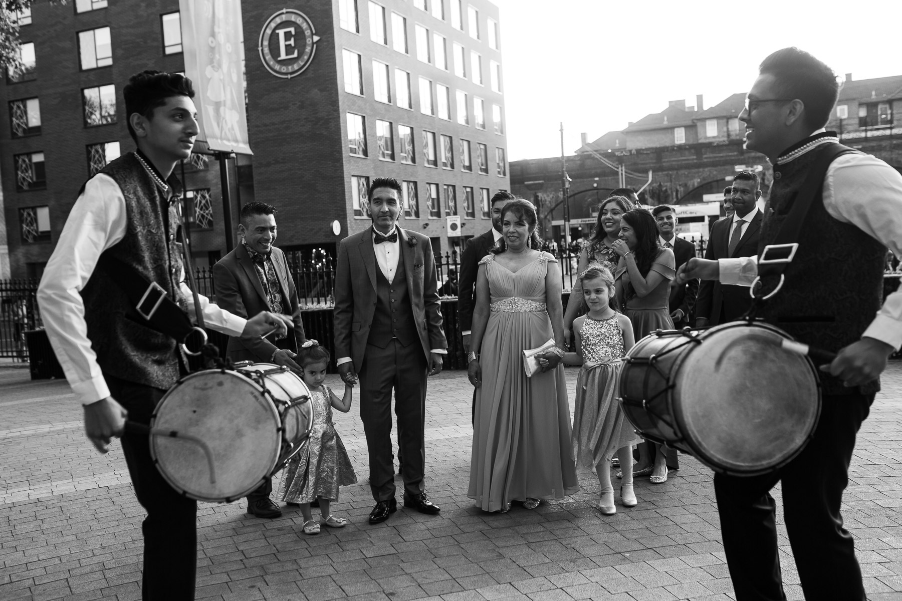 Two performers playing drums with groom preparing to walk in to the venue